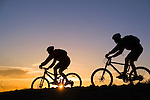 A photo of a couple Mountain Biking At Sunset