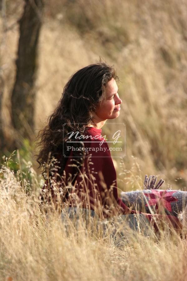 A Native American Indian women sitting in the fall grasses in South Dakota
