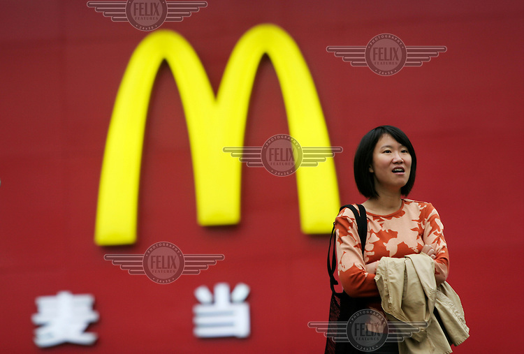 A woman stands in front of a McDonald's billboard in downtown Shanghai.