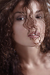 Sensual beauty portrait of a young woman looking through her long curly brown hair, closeup of beautiful face with natural makeup