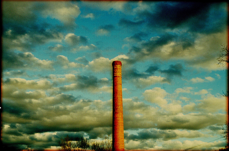An industrial chimney with clouds