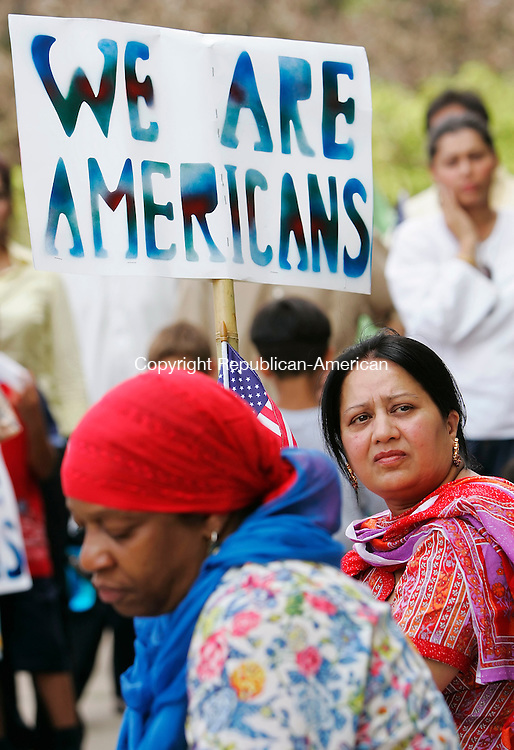 HARTFORD,  CT 05 August 2005 -080505BZ05- Khaleeda Chaudhry, of Ellington, right, holds a sign and American Flag while participating with members of Connecticut's Muslim community, Pakistani Americans and people of Pakistani heritage residing in Connecticut, during a rally against the ideology of hatred and terrorism at the State Capitol in Hartford Friday afternoon.<br /> Jamison C. Bazinet Photo
