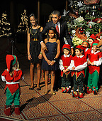 United States President Barack Obama gestures to a wayward child to join the group of other children also dressed in Christmas elves costumes for a photo at a Christmas In Washington celebration at the Building Museum in Washington, DC, USA, Sunday, December 12, 2010.  Obama's daughters Malia and Sasha are at (L).   .Credit: Mike Theiler - Pool via CNP