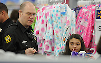NWA Media/ J. T. WAMPLER- Teresa Gallegos, 12, of Springdale gets some shopping assistance from Springdale police oficer John Lipscomb Friday Dec. 12, 2014 during the department's annual Shop with a Cop program. Around fifty officers took children shopping at the Pleasant St. Wal-Mart spending around $33,000. The funds came from donations, corporate spoonsorships and fund raisers.