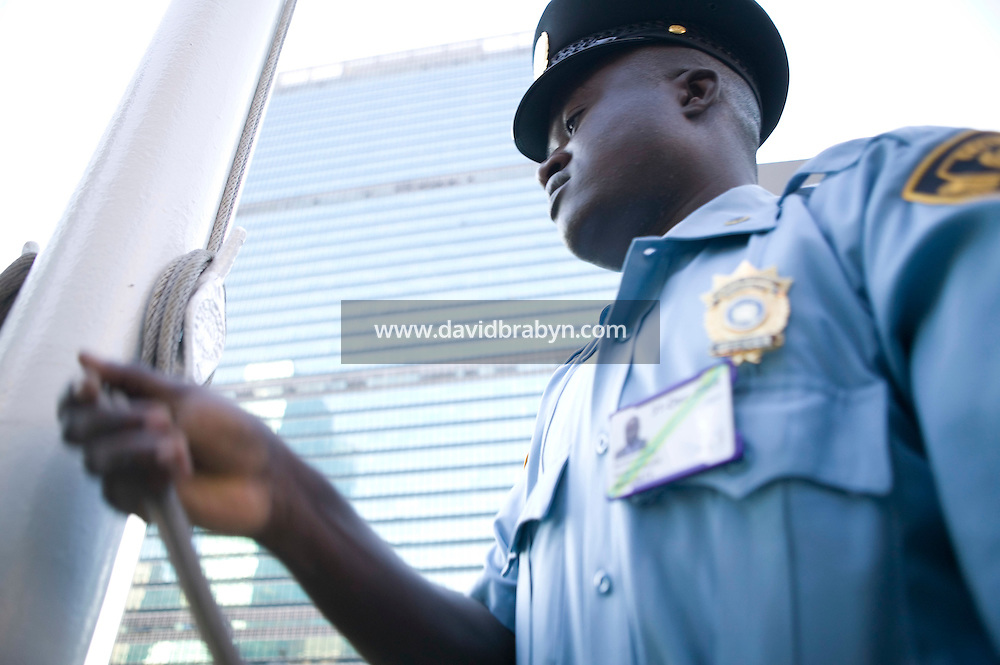 8 September 2005 - New York City, NY - A security guard raises one of 191 member state flags in front of the Secretariat building at the United Nations headquarters in New York, USA, shortly after 8am, 8 September 2005, for the first time since early this year. Construction work prevented the flags from being hoisted. The 4 by 6 feet flags are placed in English alphabetical order, from Afghanistan, at 48th Street, to Zimbabwe, by 42nd Street. They come down every day at 4pm and are stored in small boxes at the base of the poles. Photo Credit: David Brabyn