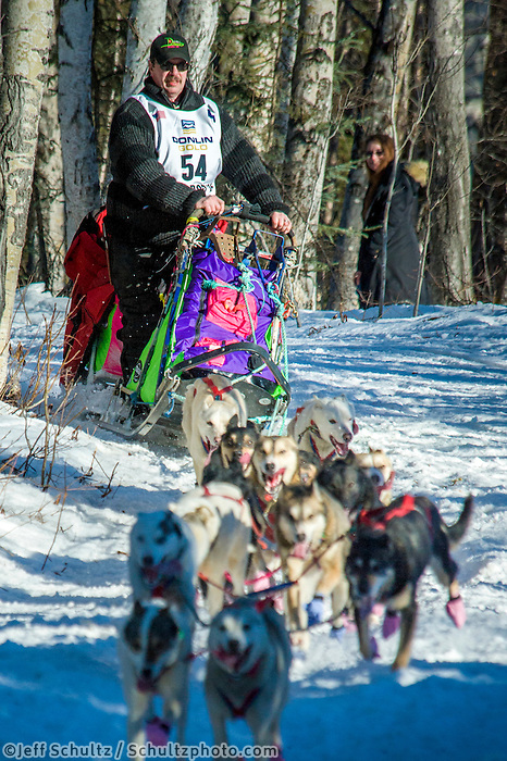 Alan Eischens  and team run down the trail on Long Lake shortly after leaving the re-start in Willow, Alaska on Sunday, March 6th during the 2016 Iditarod race. Photo by Joshua Borough/SchultzPhoto.com