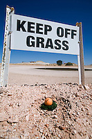 A quirky sign at the Coober Pedy golf course.  The desert course was voted in the top ten unique courses in the world, with its grassless fairways and putting greens composed of oiled sand.  Coober Pedy, South Australia, AUSTRALIA.
