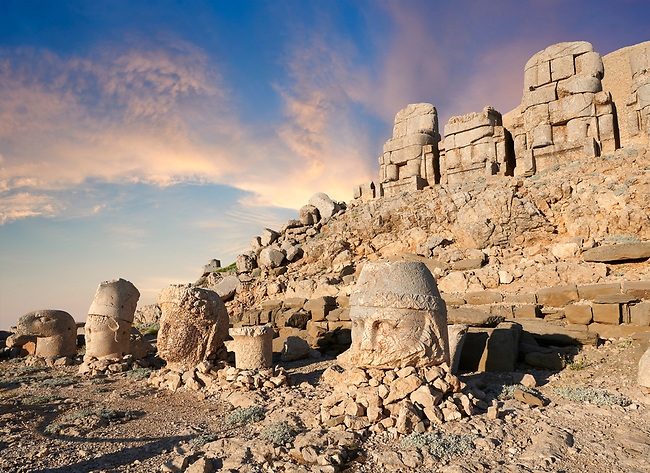Statue heads at sunset , from right, Zeus, Commagene, Antiochus, & Eagle, with headless seated statues in front of the stone pyramid 62 BC Royal Tomb of King Antiochus I Theos of Commagene, east Terrace, Mount Nemrut or Nemrud Dagi summit, near Adıyaman, Turkey