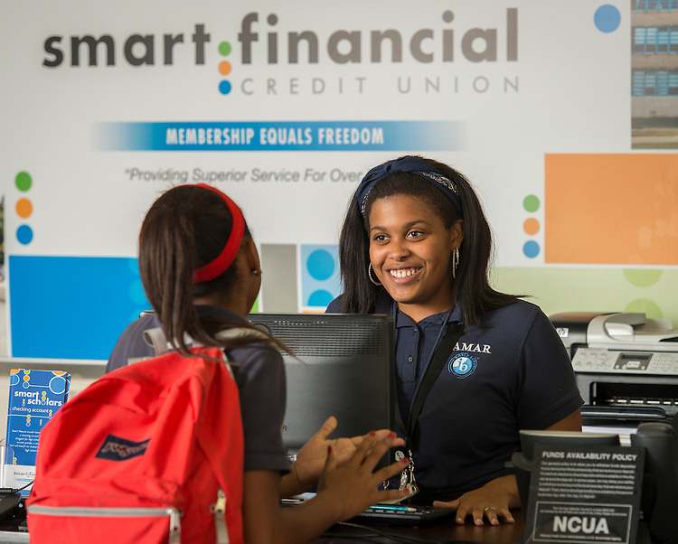 A student intern assists another student with a transaction at the Smart Financial branch at Lamar High School, October 9, 2014.