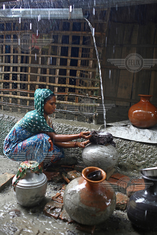 Hasina Begum (35) collects rainwater which she filters through cloth. The rainwater is a useful source of pure water which is hard to find during floods as the ground water is often contaminated by sea water.