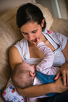 "A woman in her early twenties breastfeeding her nine month old baby girl at home while sitting on a sofa in her living room. The baby is playing, putting her fingers in her mother's mouth and touching her face.<br /> <br /> Image from the breastfeeding collection of the ""We Do It In Public"" documentary photography picture library project: <br />  www.breastfeedinginpublic.co.uk<br /> <br /> <br /> Dorset, England, UK<br /> 08/03/2013<br /> <br /> © Paul Carter / wdiip.co.uk"