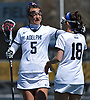 Jacqueline Jahelka #5 of Adelphi University, left, congratulates teammate Kate Beier #18 after she scored a goal in an NCAA Division II women's lacrosse game against Merrimack at Motamed Field in Garden City, NY on Saturday, April 8, 2017. Jahelka recorded two goals and five assists while Beier tallied four goals and one assist in top-ranked Adelphi's 19-1 win.