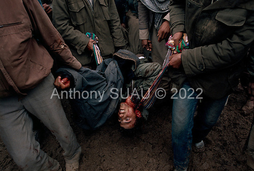 Isikveren, Turkey.April 12, 1991..A young Kurdish man is cared away after he being shot in the neck and killed by a Turkish soldier. The incident occurred during a frenzied fight for large food air-dropped into a Kurdish refugee camp. The camp housed an estimated 300,000 refugees that fled Saddam Hussein's post Gulf war persecution....In the wake of the 1991 Persian Gulf War rebellions in Southern and Northern Iraq occurred. The uprising in the Kurdish areas of Northern Iraq broke out in March, sparked by demoralized Iraqi Army troops returning from it's defeat against United States lead coalition forces in southern Iraq and Kuwait. Although they presented a threat to Iraqi President Saddam Hussein?s regime, his Iraqi Republican Guard suppressed the rebellion with massive force, as the expected US intervention never materialized. ..The faltering rebellion fueled a terrified mass exodus. The U.N. High Commissioner for Refugees called it the largest in its 40?year history. During March and early April, nearly two million of Iraqis escaped from strife-torn cities to the mountains along the northern borders and into Turkey and Iran. Their exodus was sudden and chaotic, with thousands fleeing on foot, on donkeys, or crammed onto open-backed trucks and tractors. Thousands, many of them children, died or suffered injury along the way, primarily from adverse weather, unhygienic conditions and insufficient food and medical care. Some were killed by army helicopters, which deliberately strafed columns of fleeing civilians. Others were injured when they stepped on land mines planted by Iraqi troops near the Iran border during the war. Greenpeace has estimated that at one point in 1991, an estimated 2,000 Kurds were dying every day..