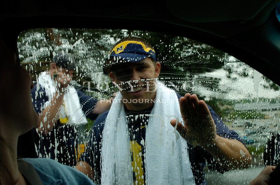 "Michigan sophomore kicker Garrett Rivas (38) waves at Farmington Hills resident Lisa K. Giles as she sits in her SUV while the football team washes her car..""Lloyd Carr Wash"" - a fund raiser by the UM Football team for Mott's Children's Hospital..Michigan Stadium.Ann Arbor, Mich. .(Photos by TONY DING/The Michigan Daily)."