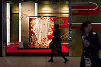 People walk past a kimono on display in a shop window in Shinjuku, Tokyo, Japan. Friday January 19th 2018