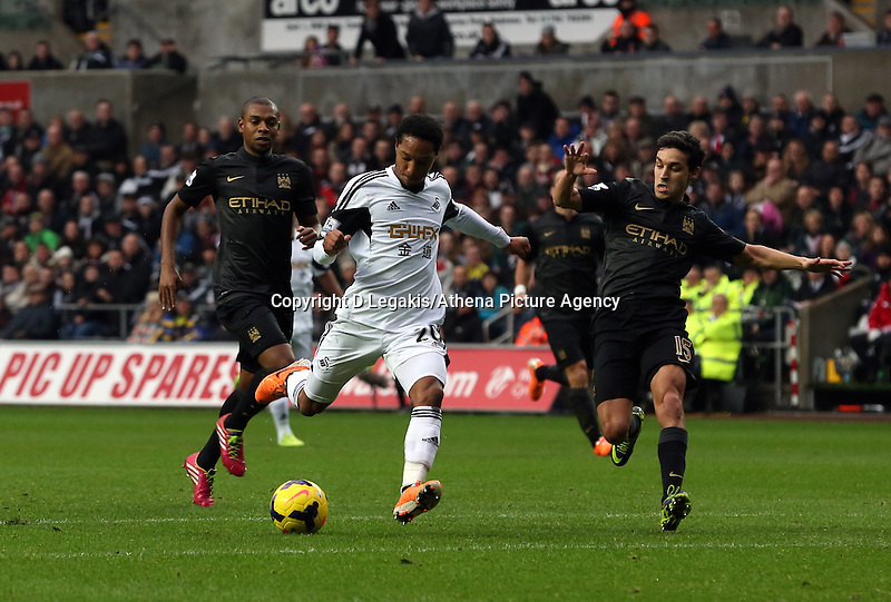 Wednesday, 01 January 2014<br /> Pictured: Jonathan de Guzman of Swansea (C) takes a shot off target, he is marked by Jesus Navas (R) of Manchester City.<br /> Re: Barclay's Premier League, Swansea City FC v Manchester City at the Liberty Stadium, south Wales.