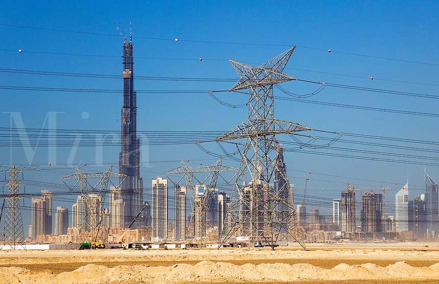 Dubai.  Skyline of the Downtown Dubai Development with the Burj Dubai and Financial Centre.  Electricity transmission lines and pylon..