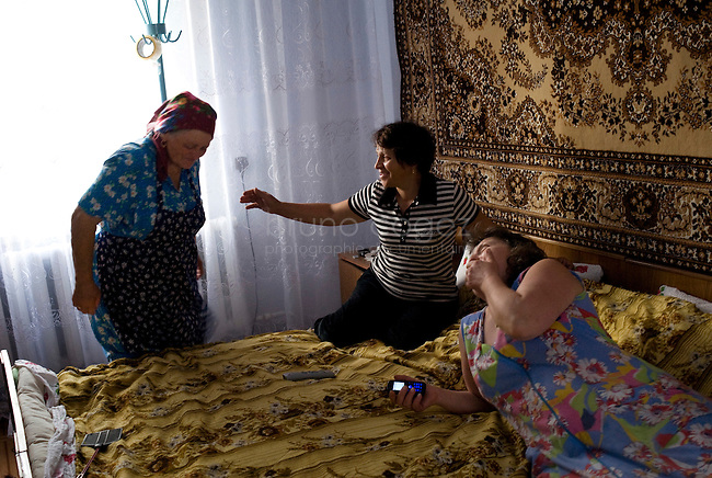 REPUBLIC OF MOLDOVA, Gagauzia, Vulcanesti, 2009/06/30..Viera and her sister Anna and the stepmother mother of Viera, Fiedorova in the bedroom of her home in Vulcanesti. In each gagauz family, someone from earning a living abroad. Viera works in Moscow and his sister in Turkey. On the occasion of the summer works in fields, everyone ends up in the family home..© Bruno Cogez..REPUBLIQUE MOLDAVE, Gagaouzie, Vulcanesti, 30/06/2009..Viera et sa soeur Anna et la belle mère de Viera, Fiedorova dans la chambre à coucher de la maison familiale à Vulcanesti. Dans chaque famille gagaouze, quelqu'un part gagner sa vie à l'étranger. Viera travaille à Moscou et sa soeur en Turquie. A l'occasion des travaux d'été dans les champs, tout le monde se retrouve dans la maison familiale..© Bruno Cogez