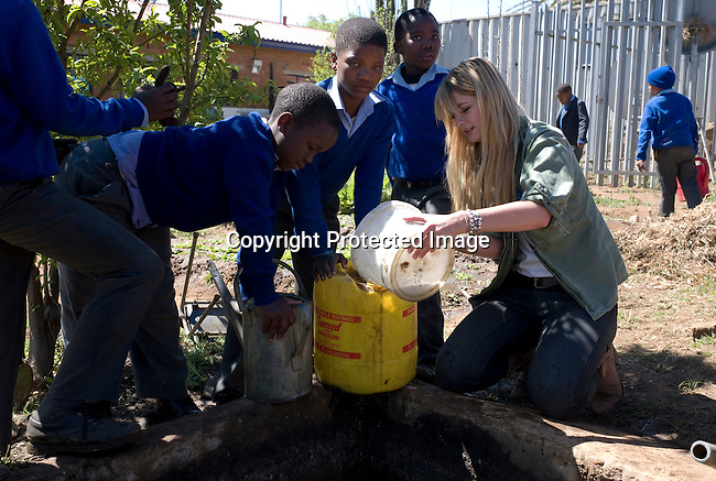 SOWETO, SOUTH AFRICA - SEPTEMBER 1: Mischa Barton, the actress and model, helps fetching water from a well at Winnie Ngwevekazi Primary School on September 1, 2008 in Soweto, outside Johannesburg, South Africa. Mischa Barton spent 2 days visiting Save The Children supported projects in South Africa, meeting school children and young children. Save The Children are helping about 51,000 children made by HIV/AIDS and poverty to access food, healthcare, social security and education. (Photo by Per-Anders Pettersson/Getty Images For Save The Children).
