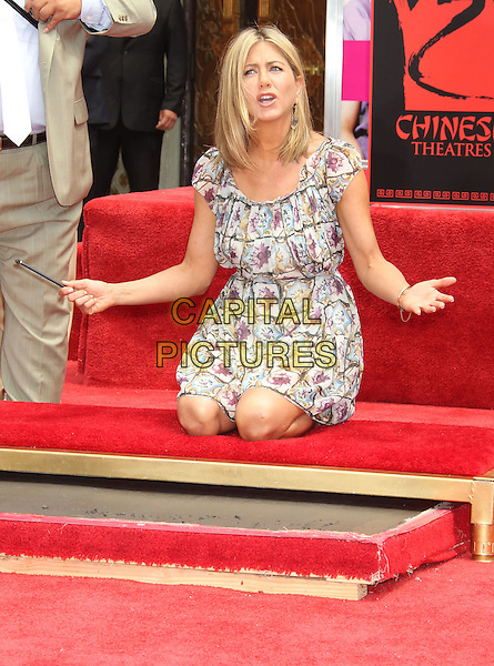 Jennifer Aniston.The Jennifer Aniston Hand and Footprints Ceremony held at The Grauman's Chinese Theatre in Hollywood, California, USA..July 7th, 2011.full length white grey gray purple floral print dress kneeling hands arms mouth open.CAP/ADM/RE.©Russ Elliot/AdMedia/Capital Pictures.