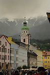 People walking along Maria Theresa street, passing pastel coloured buildings and Church , Our Lady Queen of the most Holy Rosaryon a rainy day. Innsbruck, Tyrol,Austria.