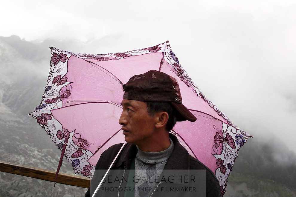 A local man stands near the Hailuogou glacier in western Sichuan Province, China. As a result of rising temperatures on the Tibetan Plateau, the Hailuogou glacier has retreated over 2 km during the 20th century alone. Since the Little Ice Age, studies have revealed that the total monsoonal glacier coverage in the southeast of the Tibetan Plateau has decreased by as much as 30 percent, causing alarm in scientific circles.