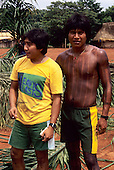 A-Ukre, Brazil. Bengoti and another Kayapo Indian warrior with black genipapo body paint with fresh palm leaves for thatch. Para State.