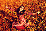 A pretty brunette dressed in vintage pink clothing sitting in fallen leaves in a park.