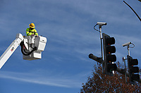 NWA Democrat-Gazette/J.T. WAMPLER Shawn Mockeridge of Bentonville backs off of a traffic signal after he installed a camera Monday Dec. 2, 2019 at the corner of Leroy Pond Dr. And Razorback Rd. Mockeridge was working with a crew from Traffic Lighting Systems to replace the signal pole.