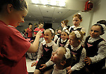 (Boston Ma 042713) Meghan Healy, left, 19, of Boston, applies a little make up to Caroline McCarthy, 7,  as fellow dancers wait their turn, Saturday night at the Back Bay Event Center. The children here are all members of the Clifden Academy, the Irish Step dancing group Jane Richard was a member of, the 7 year old who lost a leg in the Boston Marathon bombing.   Step dancing groups from through out the area came together Saturday night to raise money for the Richard family, the event was called Dance Out For Jane.. (Jim Michaud Photo) for Sunday