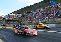 Jul, 20, 2012; Morrison, CO, USA: NHRA funny car driver Cruz Pedregon (near lane) races alongside Jeff Arend during qualifying for the Mile High Nationals at Bandimere Speedway. Mandatory Credit: Mark J. Rebilas-
