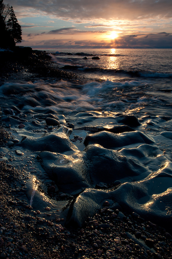 Sunrise over Lake Superior at Cascade State Park, Minnesota as the Cascade river flows into Lake Superior
