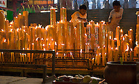 Attendants wearing the all-white outfits which are required for this festival keep alight the many giant candles at the 200 year old San Jao Sien Khong Chinese Shrine in Bangkok during the ten day Buddhist-Taoist Vegetarian Festival which is intended to purge meats and other heating foods from the body.
