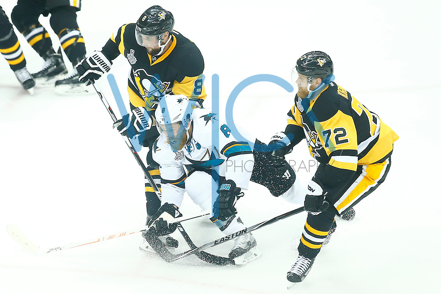 Brian Dumoulin #8 of the Pittsburgh Penguins and Joe Pavelski #8 of the San Jose Sharks collide while reaching for the puck in the first period during game two of the Stanley Cup Final at Consol Energy Center in Pittsburgh, Pennslyvania on June 1, 2016. (Photo by Jared Wickerham / DKPS)