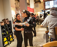 Servers deliver orders at the new Smashburger restaurant in the shadow of the Empire State Building in New York on its grand opening day, Thursday, April 10, 2014. The popular Colorado chain, which has a cultish following, opened its first Manhattan outpost  bringing their burgers, smashed to order to the Big Apple. The fast casual restaurant has a loyal fan base and has 260 restaurants worldwide. The franchise welcomed their Manhattan customers by offering a free Classic Smashburger to each patron all day, with the line eventually stretching around the block.  (© Richard B. Levine)
