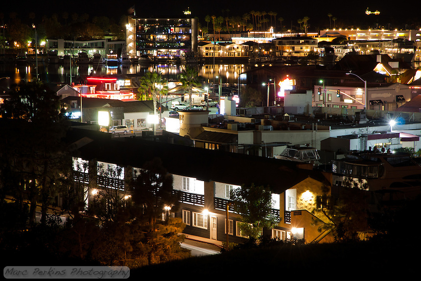 A view of west Newport Beach's Newport Harbor as seen at night from Ensign View Park.  In the foreground are buildings surrounding the Pacific Coast Highway (PCH); the back of the 2436 Pacific Coast Highway office building (that looks like a motel) is prominent, as is the Bayport Yachts round turret and Joe's Crab Shack.  Behind that are buildings on Newport Peninsula / Balboa Peninsula that front Newport Harbor, most striking among them is the multi-story Blackman Ltd. building at 3388 Via Lido Drive, with the parking structure at the Lido Marina Village on the right.  Behind those and the palm trees lie two open-ocean oil platforms (one above the Blackman building, and one above the parking structure), which almost look as if they're floating in space.  This image is a minimally manipulated single-frame, long-exposure capture.