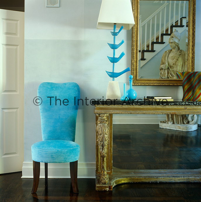 An antique console table is situated next to a contemporary chair upholstered in bright turquoise in the entrance hall of this house in East Hampton