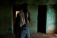 """Thomas, 28 smokes while doing drugs in an abandoned compound    in Monrovia, Liberia on  Wednesday March 21 2007..Melvin, 29 AKA """"Dad"""",  John, 29 AKA """"Desperate Soldier, Thomas 28 AKA """"Bullet Patrol"""", Leroy, 28, AKA """" Pussy Mechanic"""" and Steven 27 AKA """"Field Marshall"""" are all former child soldiers that found each other on the streets after the last round was fired in Liberia. Since then they """"Hustle"""" to put some food in their stomachs and buy some drugs to """" make them forget about their lives""""..ALL NAMES HAVE BEEN FICTIONALIZED TO PROTECT THE IDENTITIES OF THE 5 MEN."""