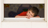 Young boy with red shirt looks out window