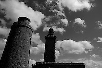 Ancient and modern lighthouses standing side by side against a cloudy sky, Cap Fréhel, Brittany, France.
