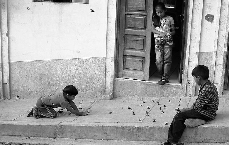 02.2010  Coroico (Bolivia)<br /> <br /> Garçons en train de jouer a la guerre avec des billes et des petits soldats.<br /> <br /> Boys playing war game in the street with balls and small soldiers.