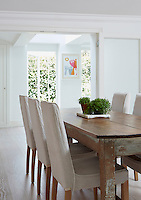 The dining area is furnished with a distressed kitchen table and chairs in loose covers and opens through French windows into the garden