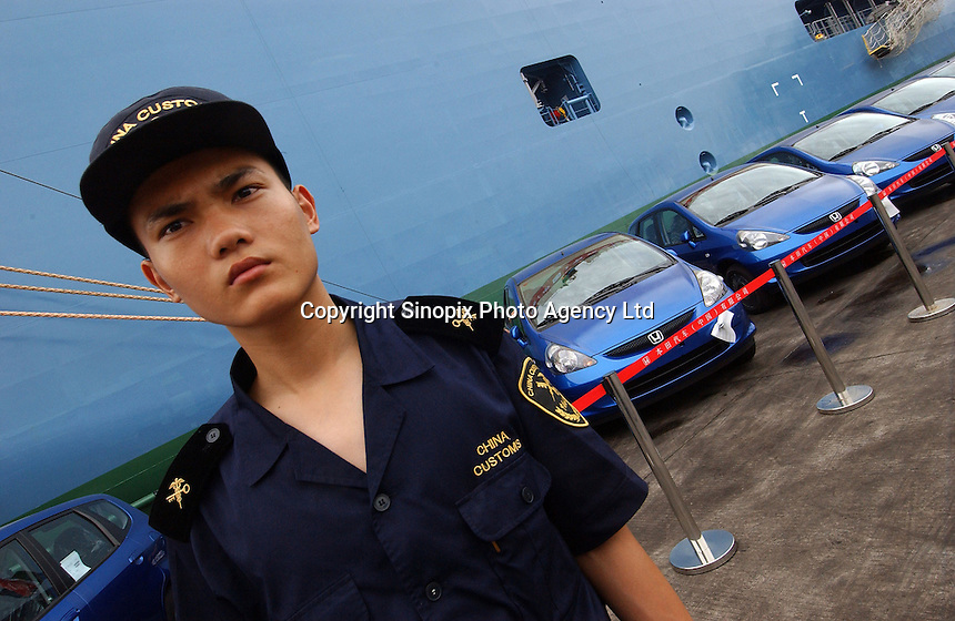 Customs officers check newly produced Honda Jazz motor cars that  are lined up for export at a port in Guangzhou, China prior to a ceremony for the first cars exported. Honda Motor Export Plant in Guangzhou, China, produce and export the Honda Jazz model. .