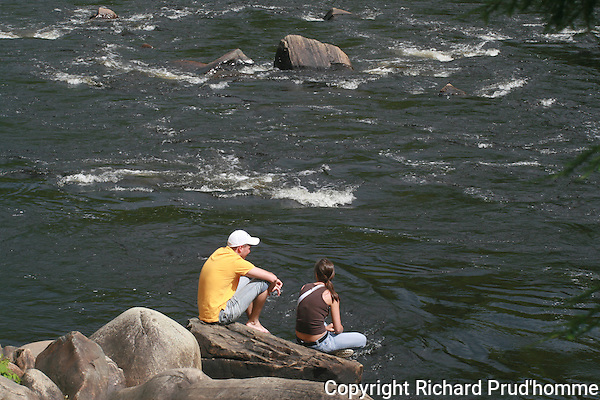 A young man and women are sitting on a rock along the Ouareau river in Rawdon, bellow the Darwin falls