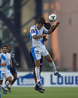 Puebla FC midfielder Felipe de Jesus Ayala (30) and New England Revolution midfielder Shalrie Joseph (21) battle for head ball. The New England Revolution defeated Puebla FC in penalty kicks, in SuperLiga 2010 semifinal at Gillette Stadium on August 4, 2010.