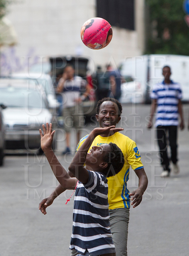 Migranti all'esterno del centro di accoglienza 'Baobab' presso la stazione Tiburtina a Roma, 16 giugno 2015.<br /> Migrants play outside of the 'Baobab' refugees center in Rome, 16 June 2015. Italy is facing a huge flow of migrants brought to Sicily after rescue at sea, many of whom are trying to join their relatives in northern Europe. <br /> UPDATE IMAGES PRESS/Riccardo De Luca