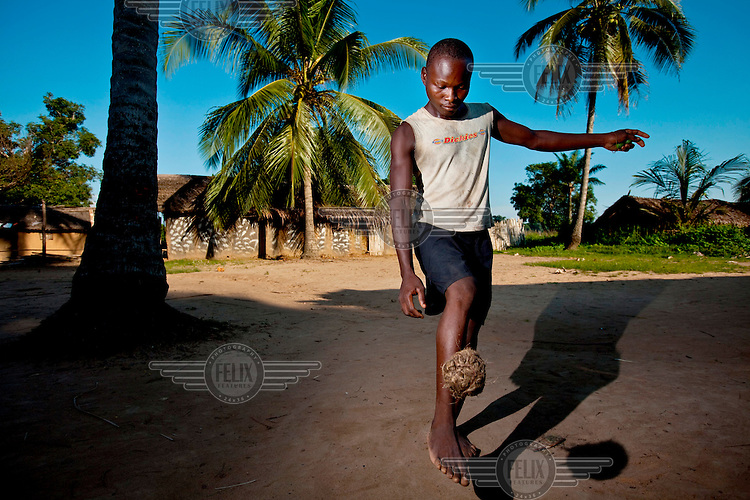 A youth plays football with a coconut.