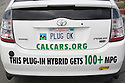 A rear view of a plug-in hybrid Toyota Prius car with 'PLUG OK' license plate and stickers promoting CalCars.Org and 100+ MPG (miles per gallon). The depicted car has driven in a Step It Up 2007 protest rally calling for increased vehicle fuel efficiency to help reduce CO2 emissions related to global warming. San Francisco, California, USA