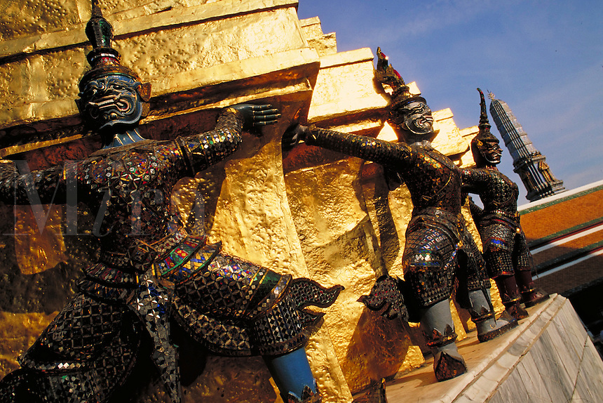 Ornately detailed statues holding up gold plated wall at the Grand Palace. Bangkok, Thailand.