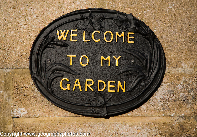 Close up of a 'Welcome to my Garden' sign fixed on wall of a house